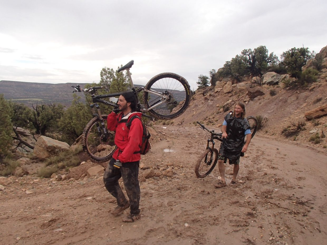 Greg Grasso, left, and Pete Owen struggle on the fifth day with deep, sticky mud. The group of eight ended up turning around to be shuttled through most of the stretch the following day.