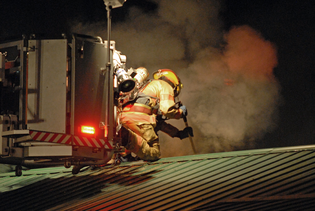 Craig firefighters step off Ladder 1's elevated platform Tuesday night to attack a home blaze from the roof.
