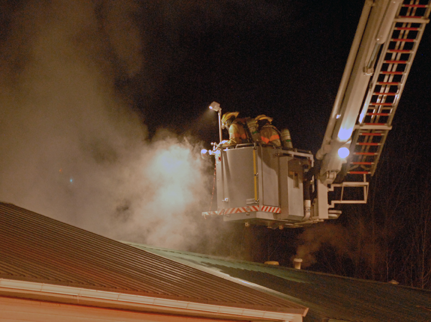 Craig Fire/Rescue firefighters hover on an elevated platform above the roof of a home fire Tuesday night in Craig. Craig Police officers were first on scene and were able to pull one of two occupants out of the burning home.