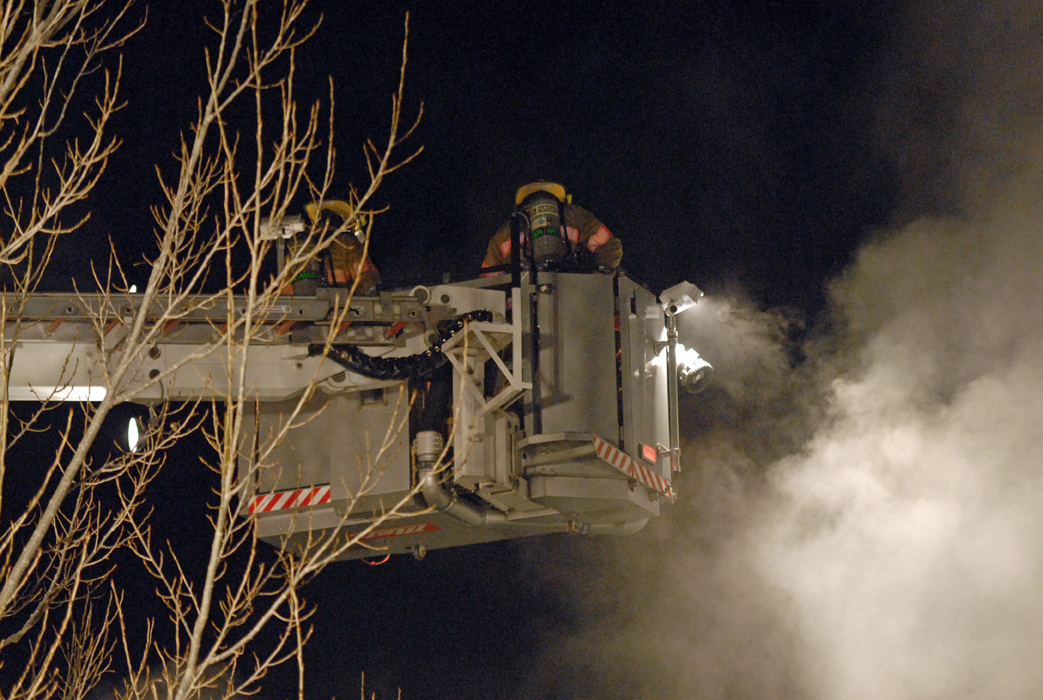 A Ladder 1 operator pulls back on the controls of the engine's elevated platform to get a pair of firefighters out of a smoke cloud during a home fire Tuesday night in Craig.