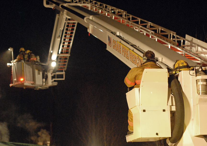 A Craig Ladder 1 operator moves two firefighters into position Tuesday night to fight a home fire from the roof.