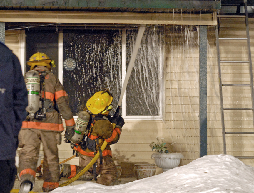 Firefighters Tuesday night pump compressed air foam into the roof of a home on Woodland Ave. during a fire.