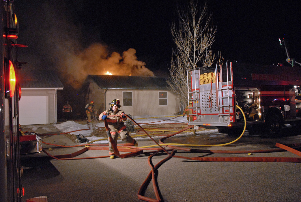 Craig firefighters arrive Tuesday night at the scene of a home fire at 1912 Woodland Ave. A 911 call at 7:46 p.m. alerted authorities to the fire.