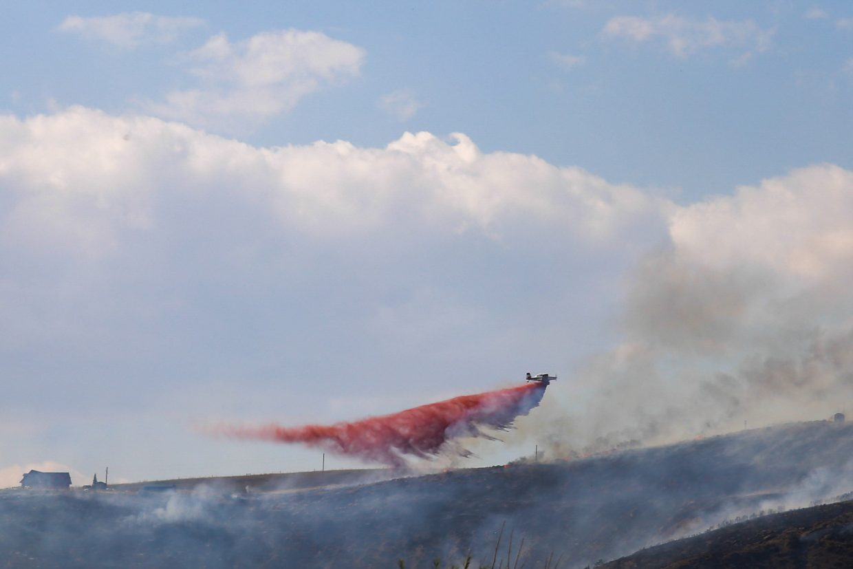 An aircraft drops fire retardant on the Cog Fire near Hayden.