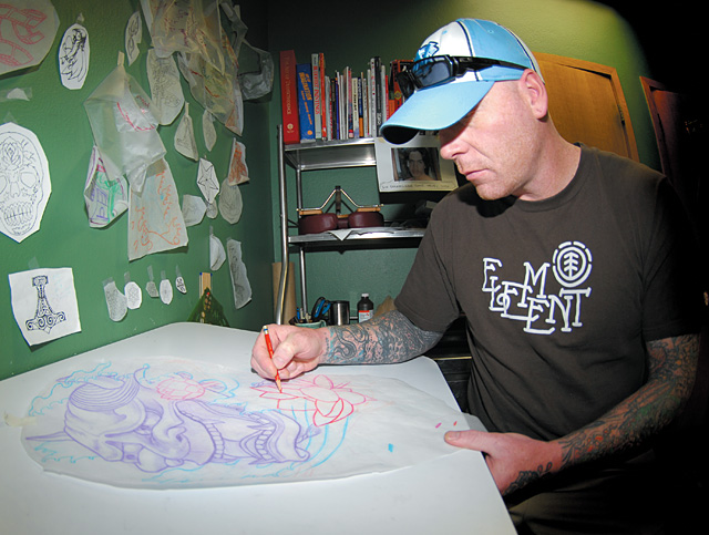 Brad Cramer sketches a tattoo in his back room. Truth Tattoo is a custom shop where almost every tattoo is designed by the tattoo artist.