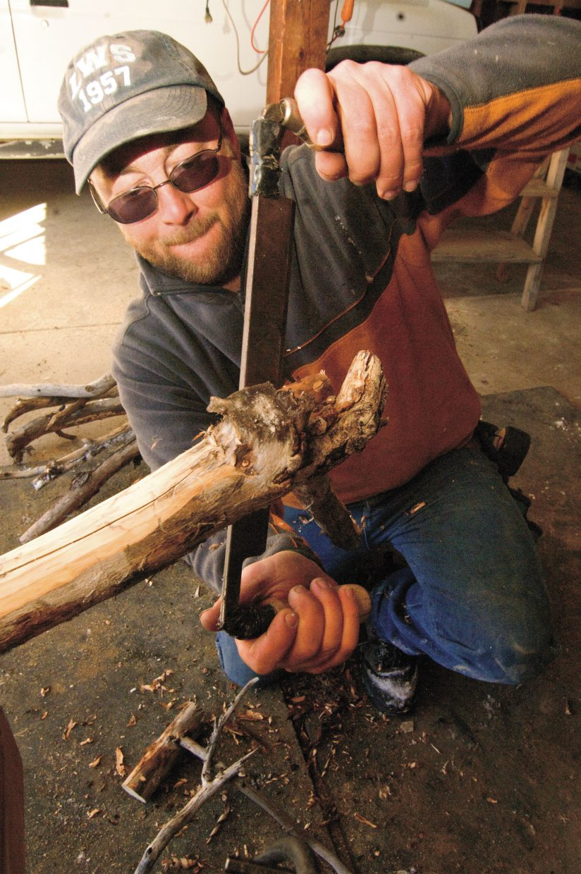 Matt Graves strip a piece of natural wood that he hopes to use for an armrest on one of his chairs.