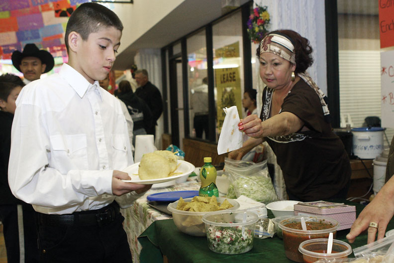 Juan Guiterrez, 11, carries gorditas made by Socorro Prieto, who is shown handing him a napkin, during Saturday's Cinco de Mayo celebration at Centennial Mall. More than 1,000 people perused the vendors and booths and took in traditional Mexican culture.
