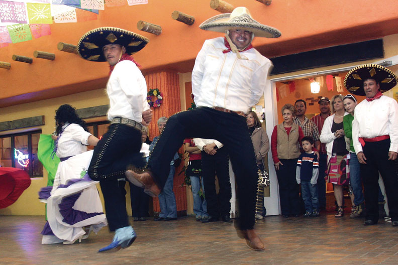 "Folklorico performers Hector M. Delacruz, left, and Jorge Flores dance together during the sixth annual Cinco de Mayo celebration Saturday. The dance, ""Pelea de Gallos,"" or Rooster Fight, tells a story throughout the performance."