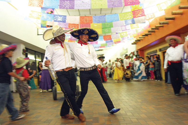 Folklorico performers Jorge Flores, on left, and Hector M. Delacruz dance together during the sixth annual Cinco de Mayo celebration on Saturday at the Centennial Mall. The two portrayed borrachos, or drunks, that failed on their attempts to attract women
