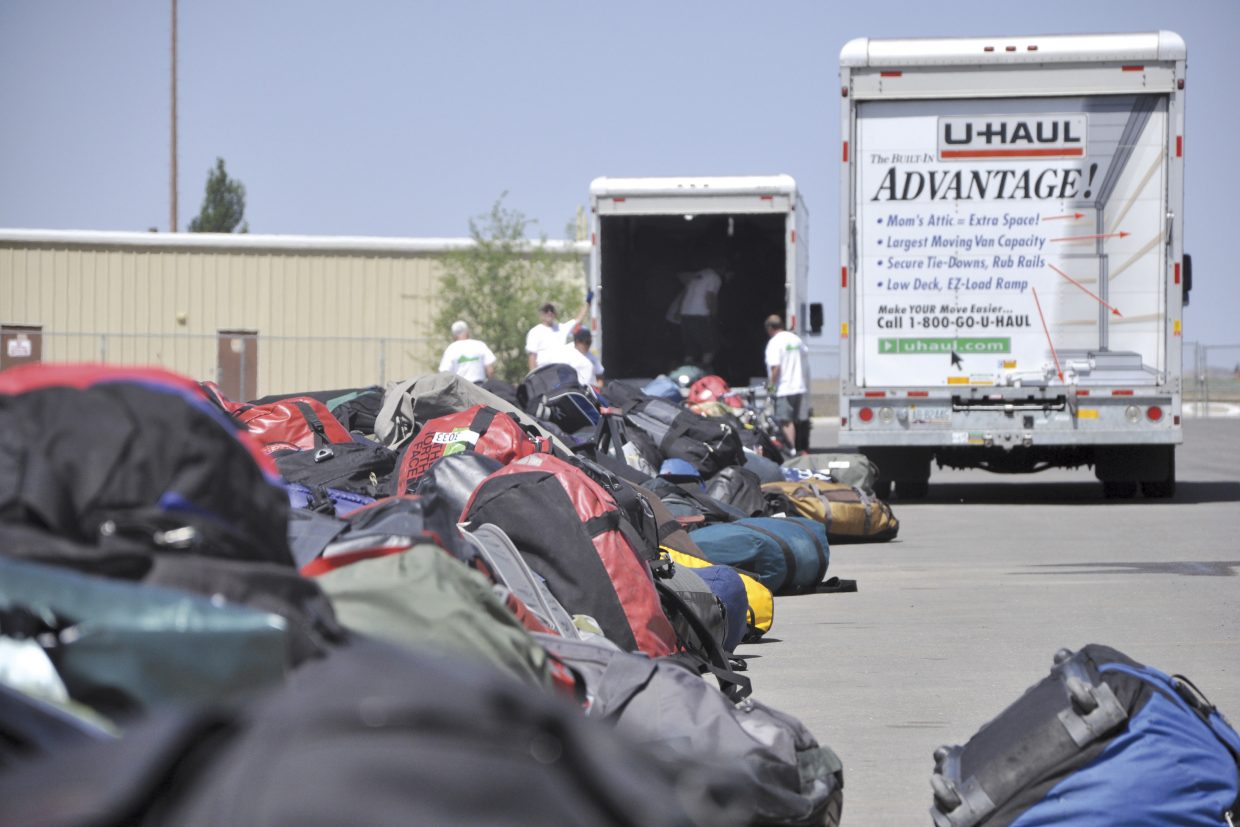 Bicycle Tour of Colorado volunteers unload riders' luggage Tuesday morning at Moffat County High School. About 1,200 people are participating in the event, said Robert Powell, Bicycle Tour of Colorado co-owner.