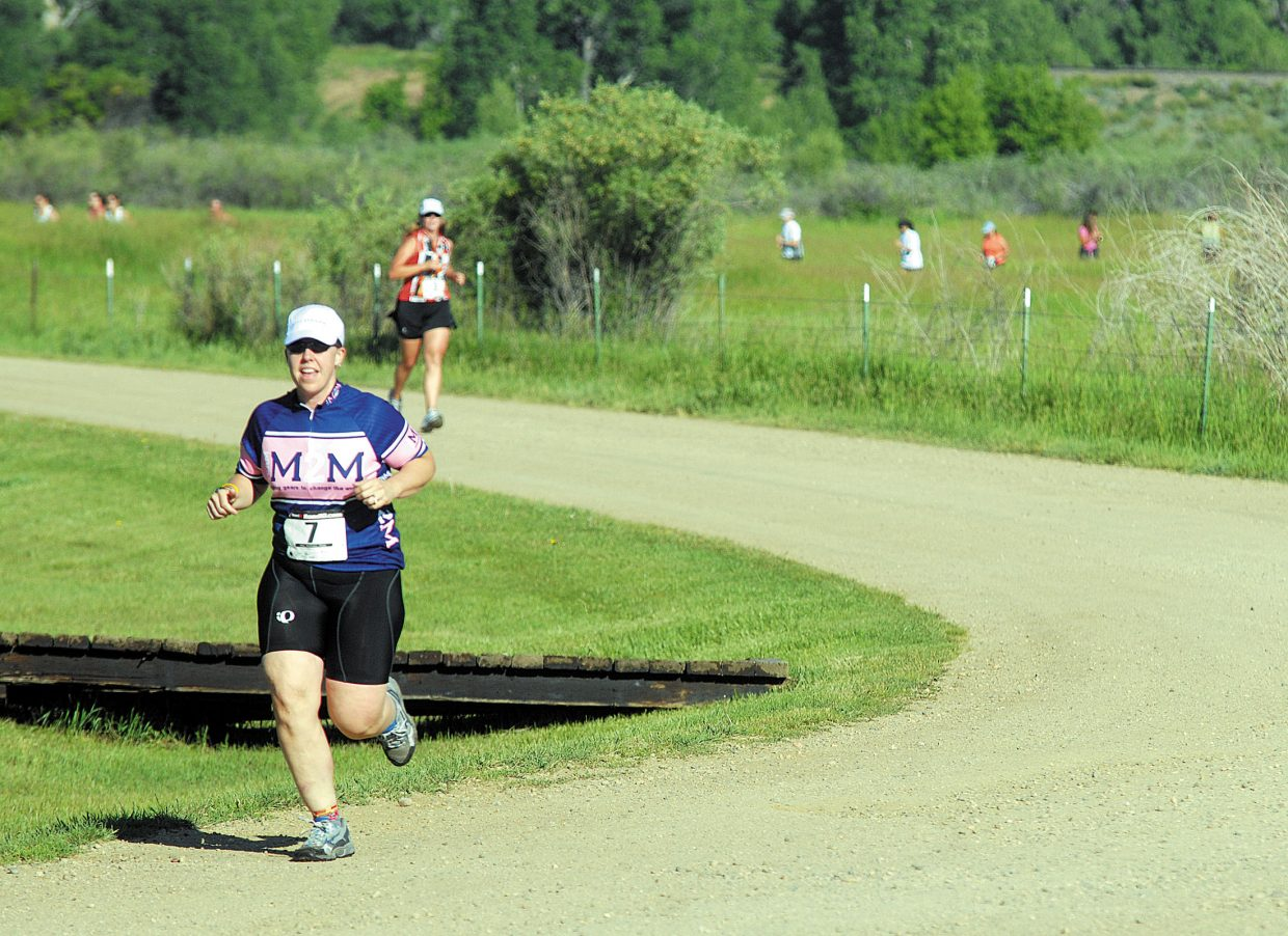 Robin Hall, left, runs the cross country course during the first leg of the Craig Duathlon.