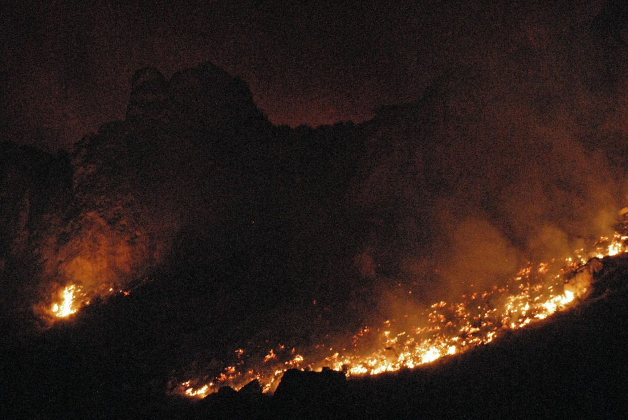 The Cedar Knob Fire begins to lie down on the east side of the blaze Tuesday night.