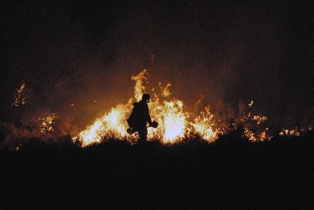 A Bureau of Land Management firefighter backfires Tuesday night while battling the Cedar Knob Fire 20 miles south of Maybell. It was the seventh confirmed fire reported in Moffat County Tuesday.