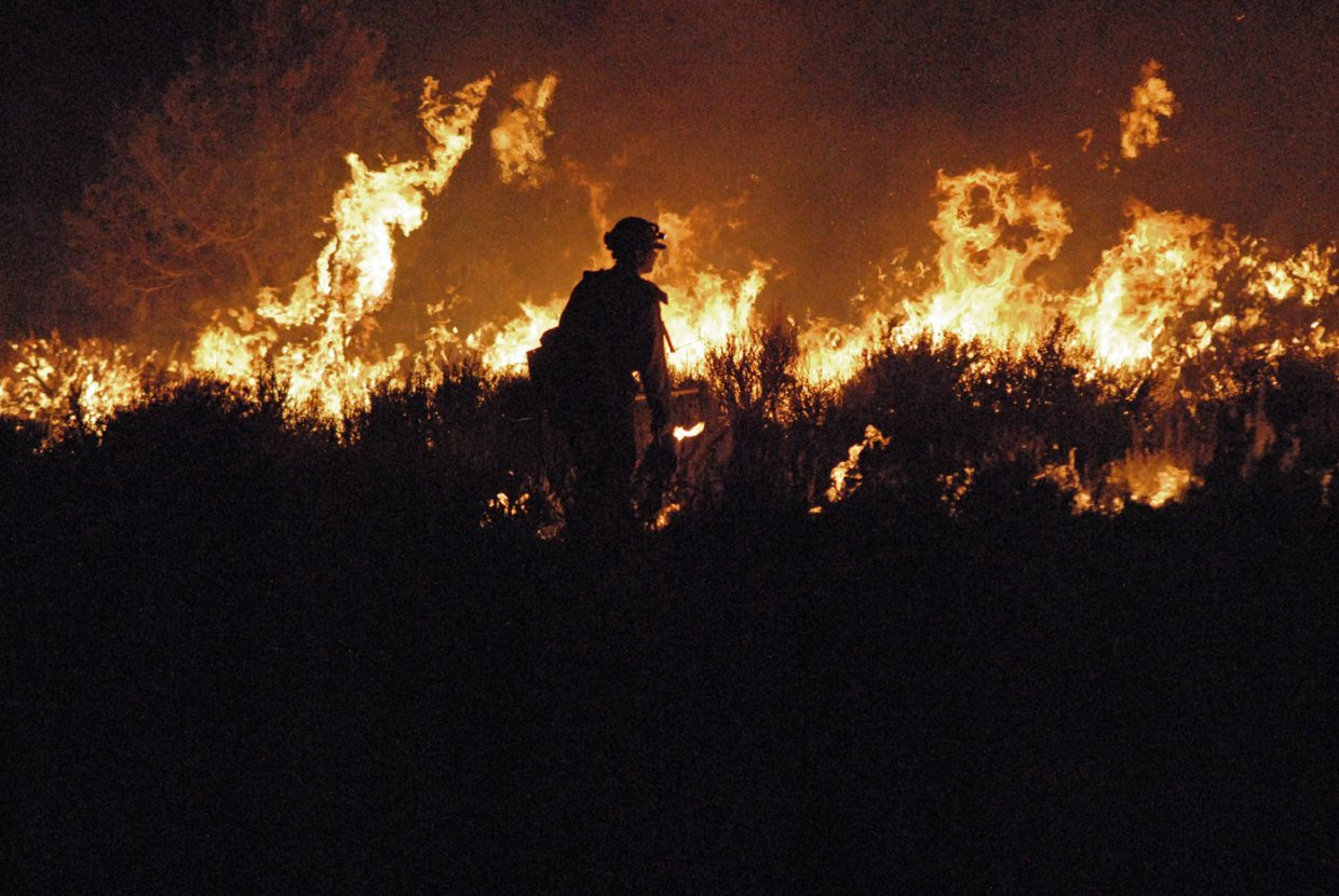 A Bureau of Land Management firefighter watches the flames during Tuesday night's Cedar Knob Fire located 20 miles south of Maybell.