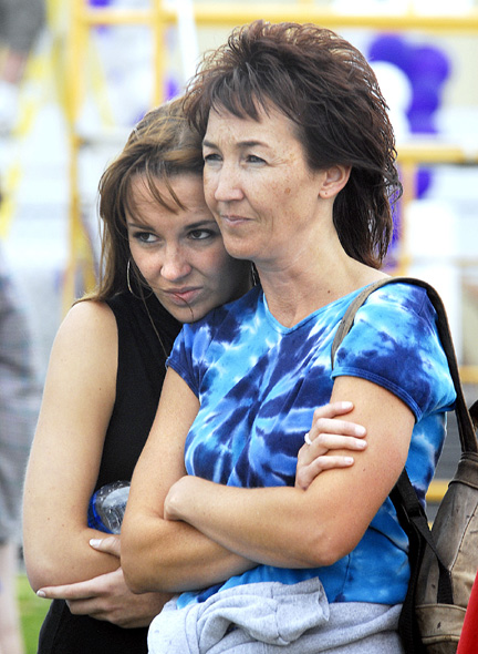 Toni Lombardi, left, and her mother, Lori Lombardi of Oak Creek, stand together as they listen to the opening ceremonies Friday night at Relay for Life. Toni performed the National Anthem at the kick-off proceedings.