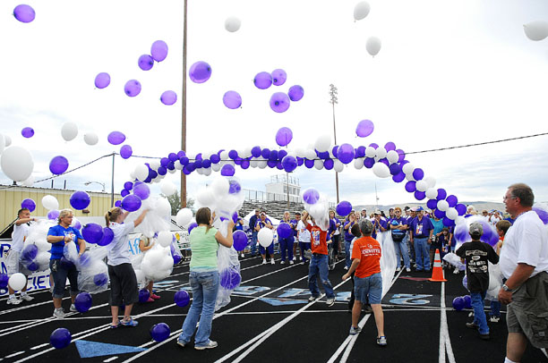 Volunteers release balloons at the start of the survivor lap Friday evening.