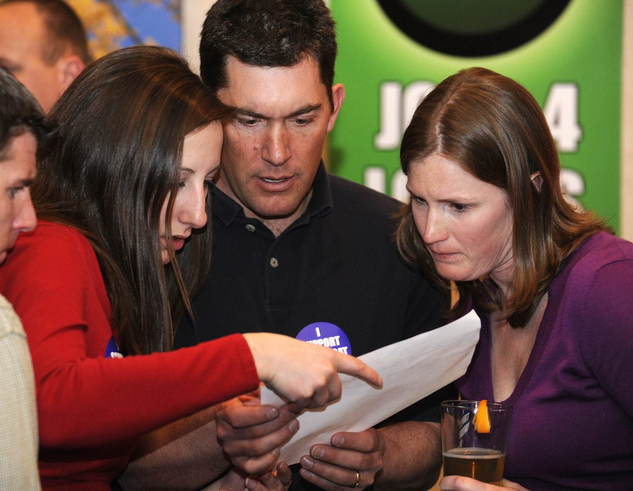 Steamboat 700 supporters, from left, Tessa DeVault, Chris Puckett and Marion Ayer look at the returns Tuesday at Rex's American Grill & Bar.
