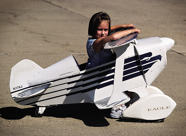 Seven-year-old Caitlin Smith checks out the Wild West Air Fest from a toy aircraft Saturday.