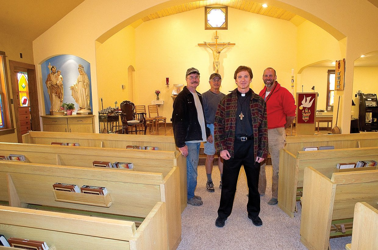 Father Ernest Bayer is joined by parishioners, from left, Tony Stich, Dwight Bruellman and Chad McGown. The men, and other members of the church, were key in getting the renovations at the church completed.