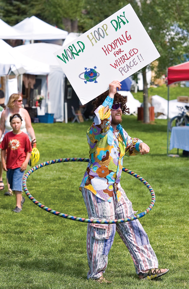 """Wayne Amsbary hula hoops through the Art in the Park Festival in Steamboat Springs on Saturday afternoon. Amsbary was leading a group of hula hoopers who were """"hooping for whirled peace."""" For more photos, see page 11."""