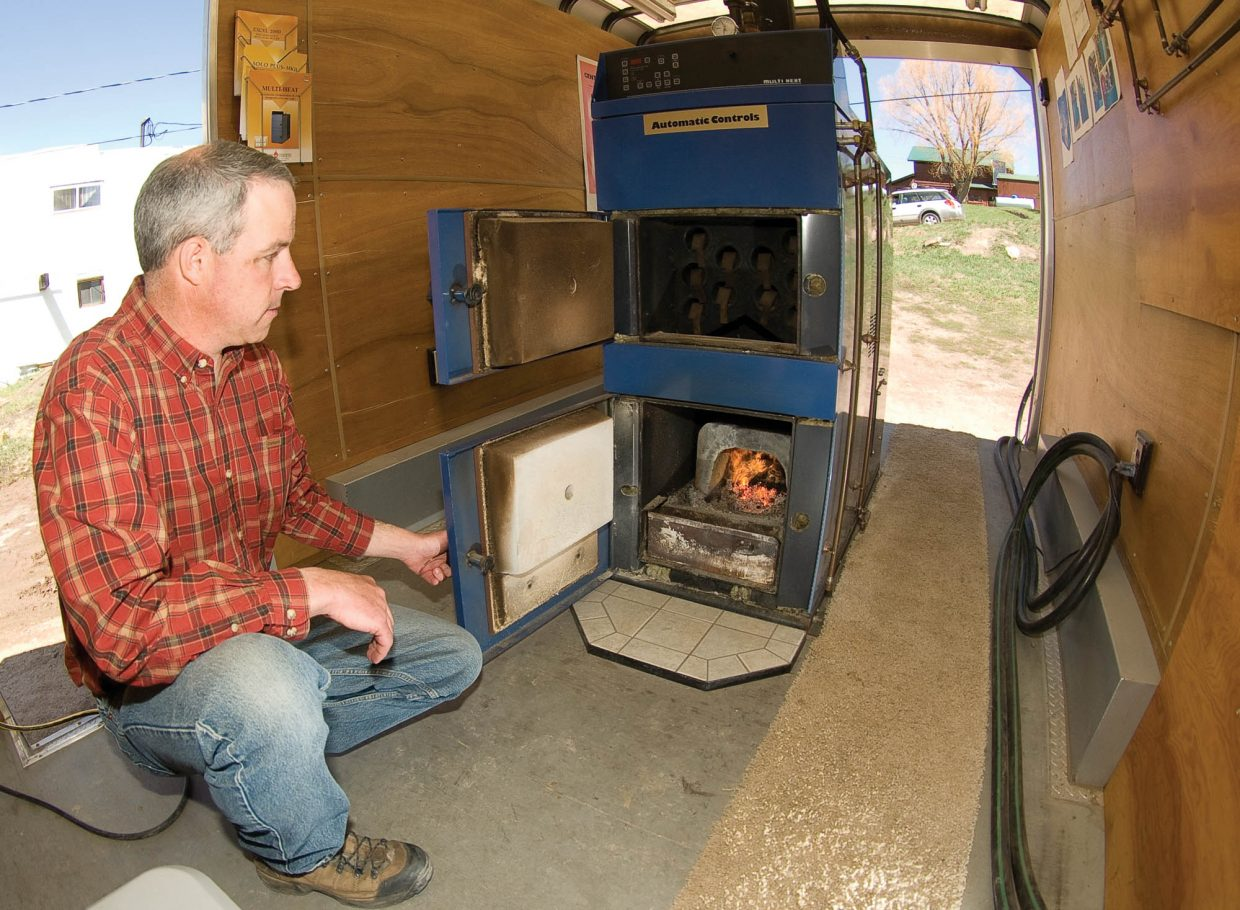 John Redmond demonstrates one of the wood-pellet boilers he sells for the Danish Company TARM USA. The pellets can be made from the scrap material created by many area sawmills processing trees killed by beetles.