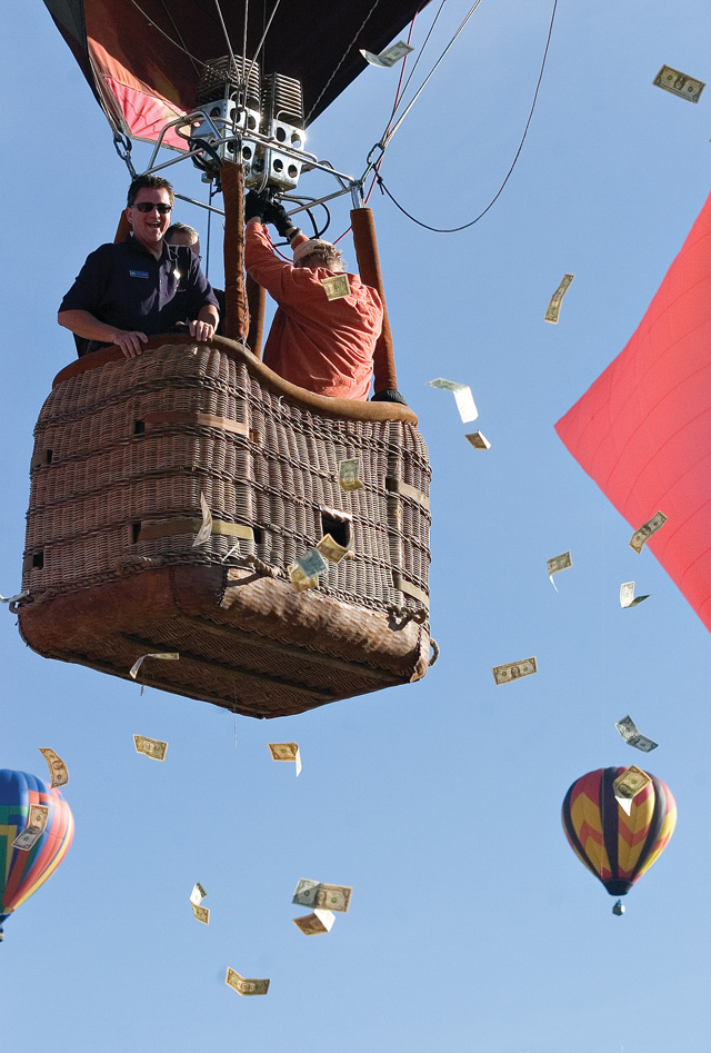 Bank of the West branch manager Hal Franke, top left, jettisons a fistful of $1 bills towards a crowd of children and spectators below after taking off from Bald Eagle Lake near Steamboat Springs on Saturday morning during the 27th annual Hot Air Balloon Rodeo.