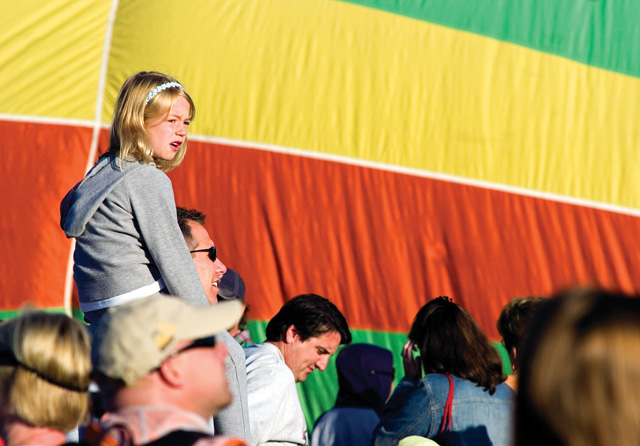 Grace Grill, top, gets a bird's-eye view of the inflating hot air ballons from her father Mike's shoulders at Bald Eagle Lake near Steamboat Springs on Saturday morning during the 27th annual Hot Air Balloon Rodeo.