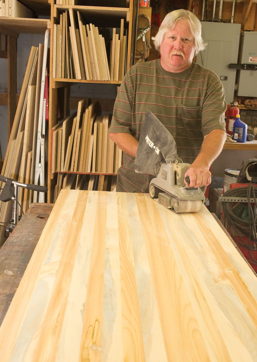 Jimmy Morton uses a belt sander to smooth beetle-killed wood that will be used for a table. Morton owns a woodworking company called Frontier Finishes, and uses beetle-killed wood to make a number of custom items.