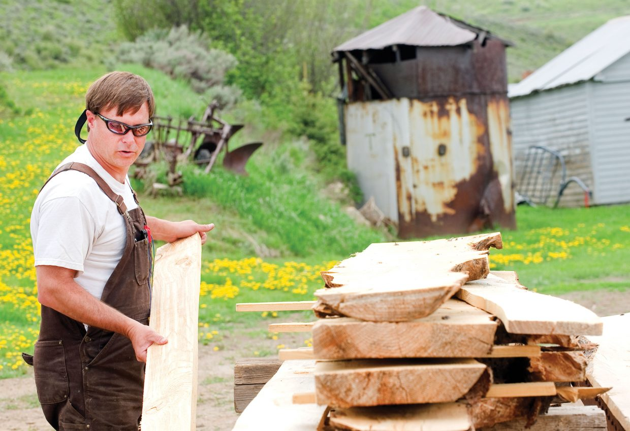 Ed Watson, of Wood Wise Productions, examines beetle-killed lumber at his sawmill near Milner. He said beetle-kill often has different characteristics depending on where it came from in the county.