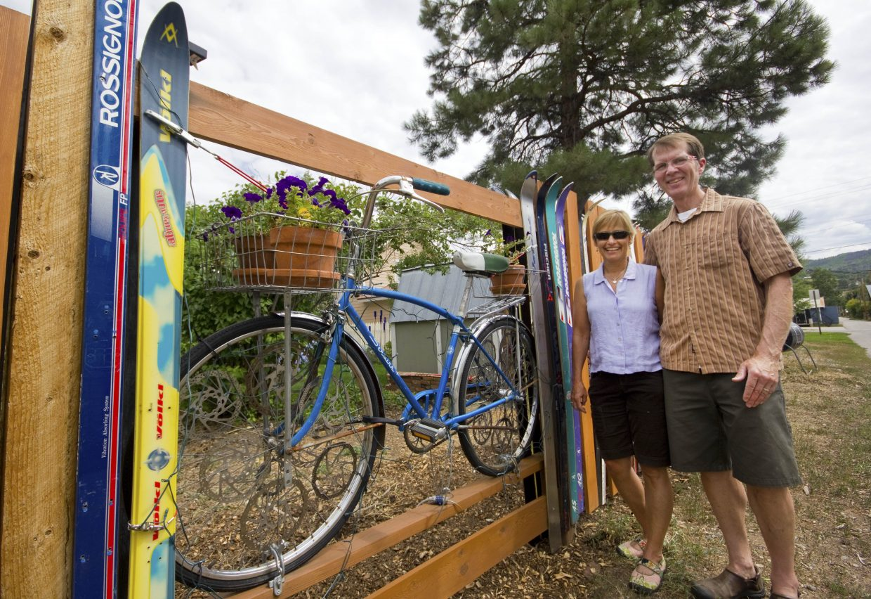 Janet Faller, left, and her husband Mark Traum, stand in front of their bike and ski fence. The fence will be part of the Art Cruiser Ride from 5 to 8 p.m. Friday.