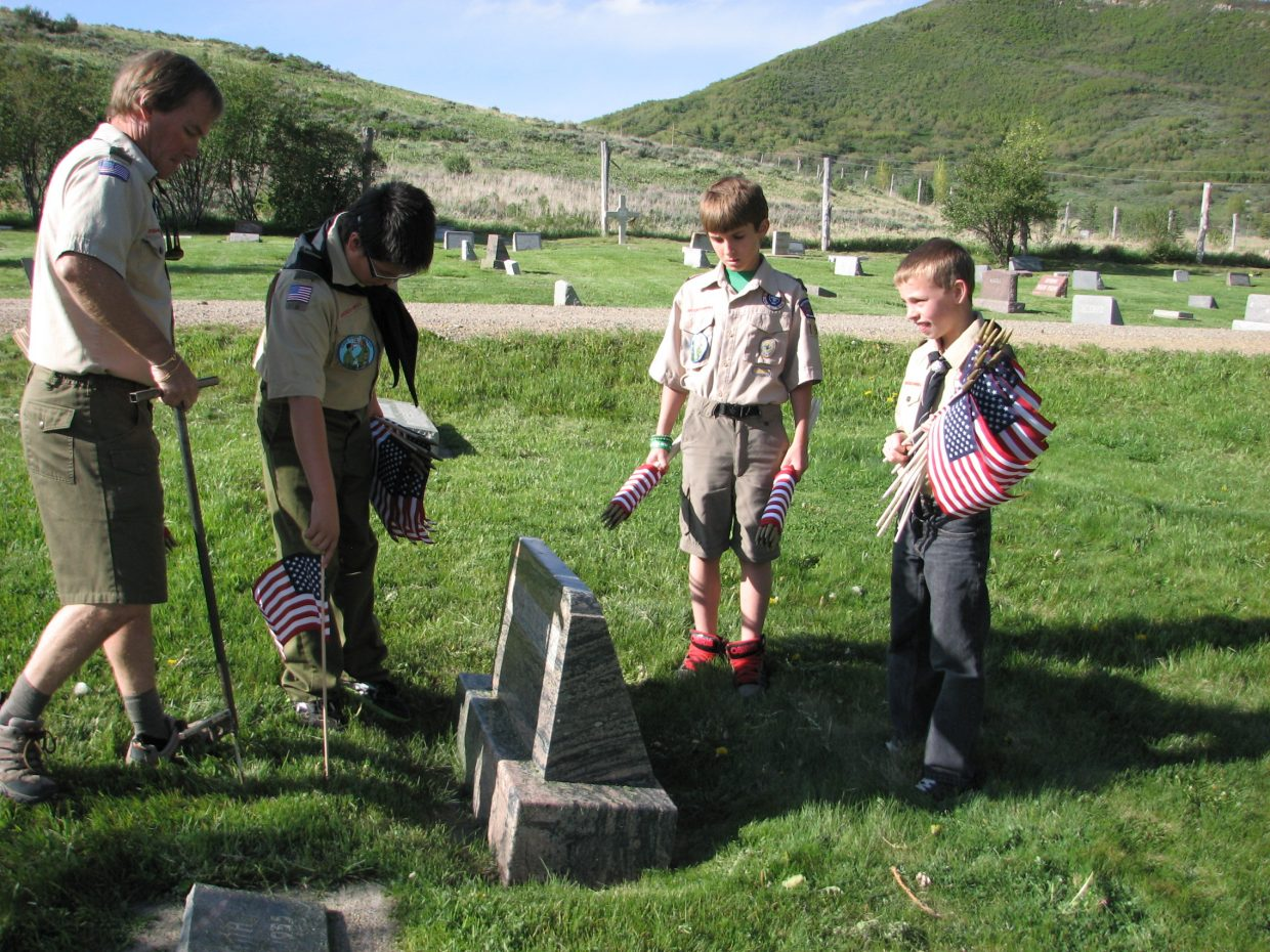 Boy Scout Leader John Paulis, from left, and Boy Scouts Justin Peretz, Ethan Paulis and Winston Vaughan place flags on veteran's graves at the Steamboat Springs cemetery. Submitted by Wendy Vaughan