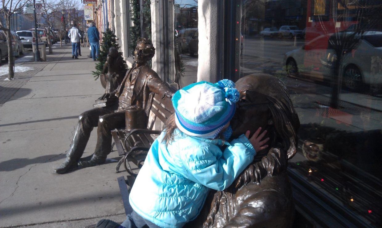 Little girl kisses Ben Franklin downtown.