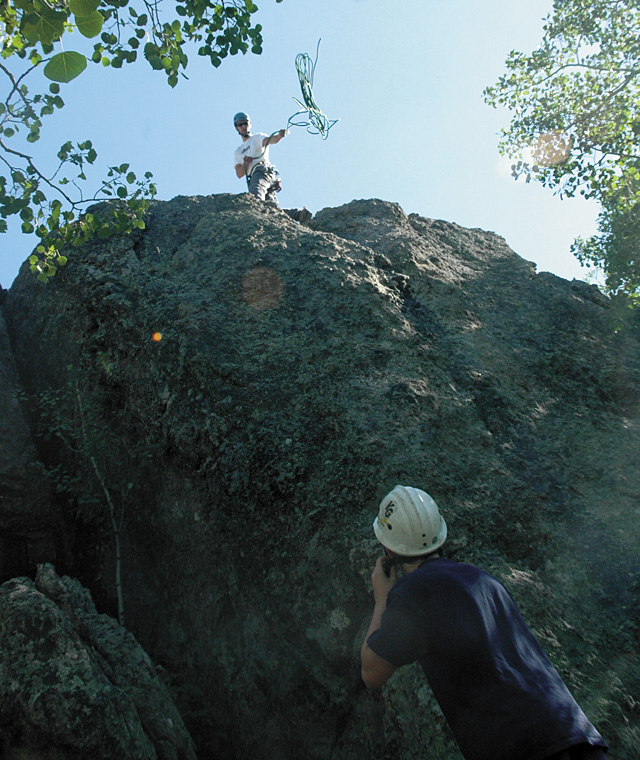 Rocky Mountain Ventrures guide Patrick Meyer, 27, sets the top rope on a bolted anchor atop one of the climbing routes at that Harrison Creek crags, south of Steamboat Springs. Bill Malley, 13, waits below to climb.
