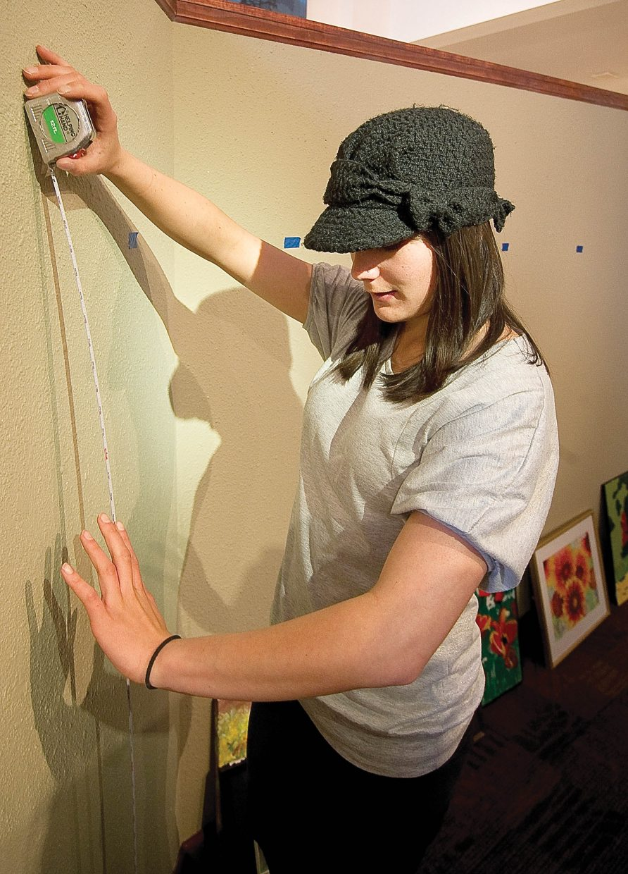 Carlee McLaughlin hangs artwork Thursday at the Center for Visual Arts Thursday as part of a show featuring work by Colorado Mountain College students.