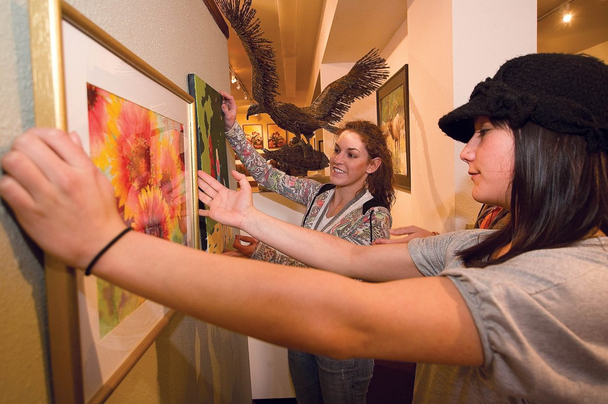 Missy Chotvacs, back, and Carlee McLaughlin hang artwork Thursday at the Center for Visual Arts on Thursday as part of a show featuring work by Colorado Mountain College students.