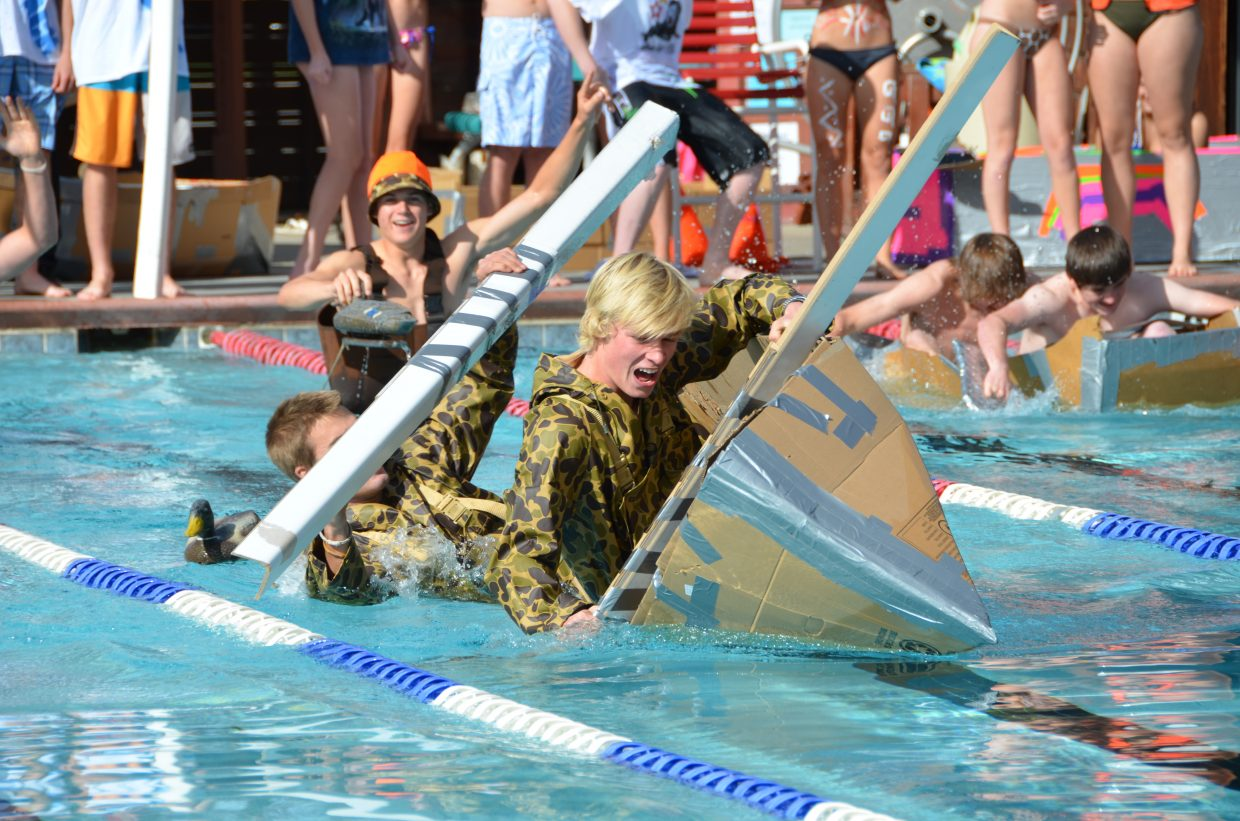 """Max Scrimgeour and Luke Farny flip their boat """"Hunters in a Canoe,"""" as teammate Lance Ostrom watches at Cardboard Classic at Old Town Hot Springs on Friday. Submitted by: Shannon Lukens"""