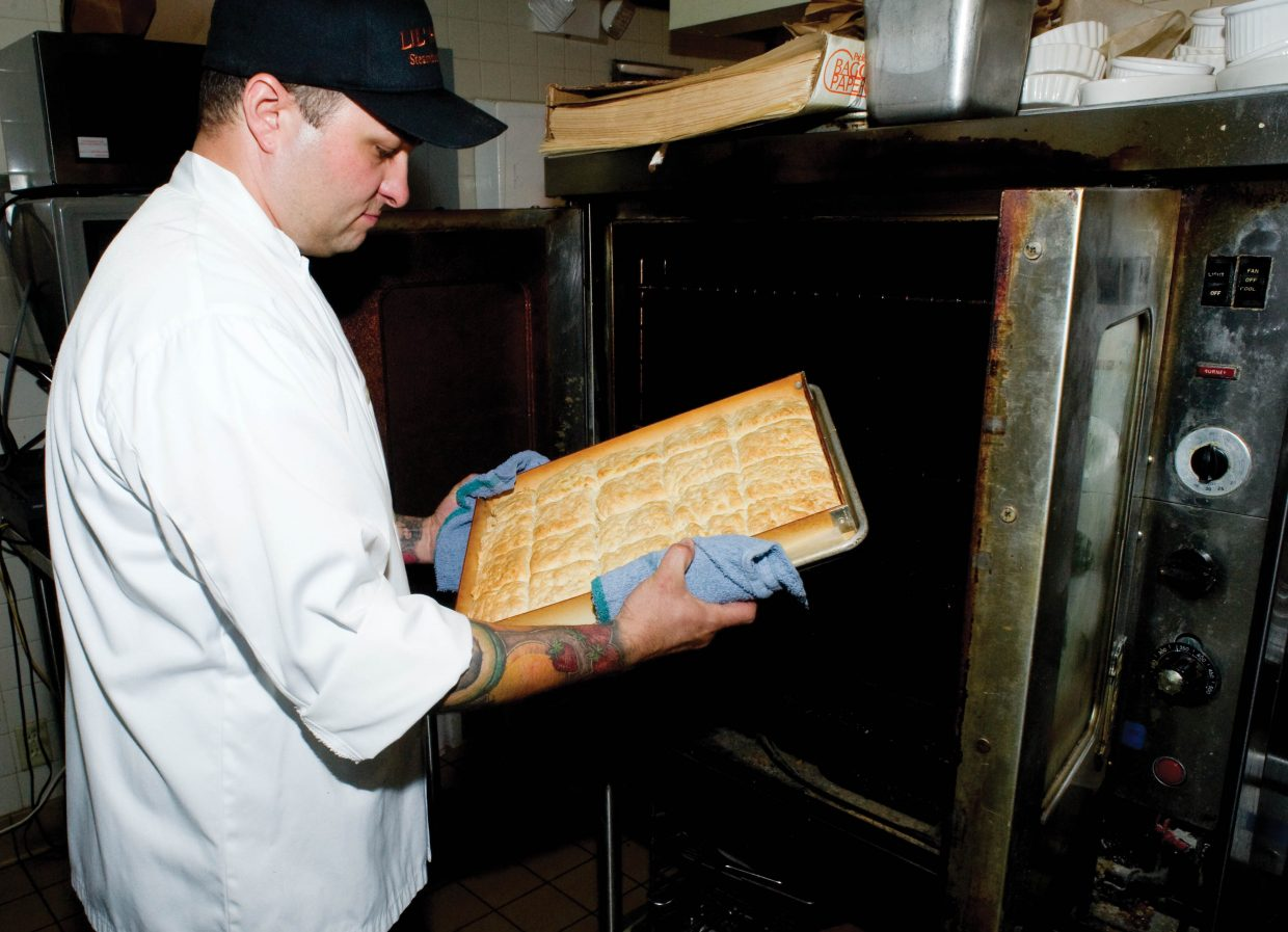 Chris McKenzie, general manager and executive chef at Big House Burgers and Lil' House, pulls hot biscuits out of the oven.