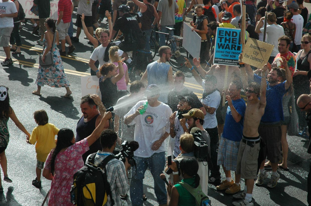 Marilyn Black Elk offers protest marchers relief from the Denver heat Wednesday.