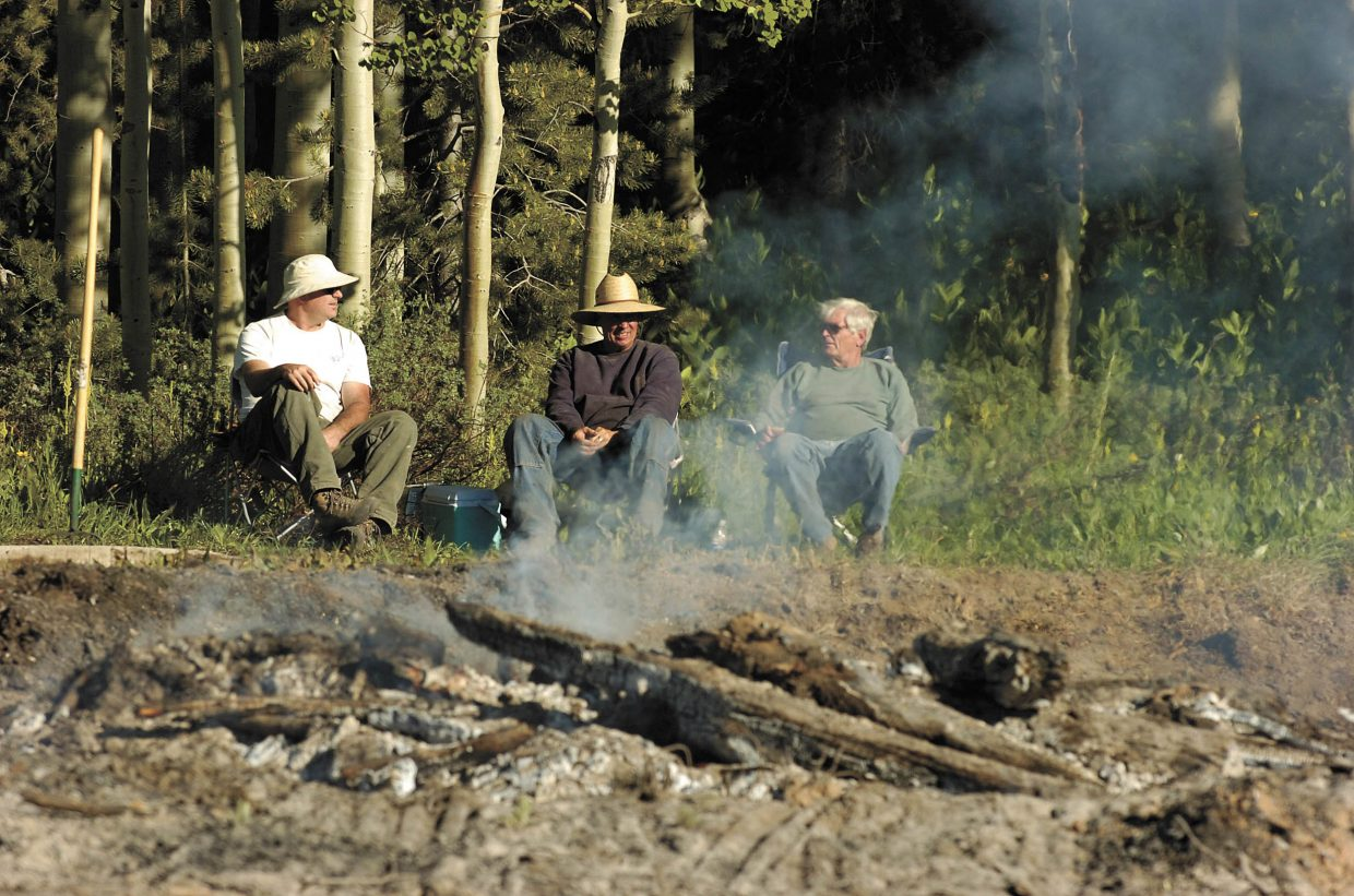 Red Creek subdivision resident Jim Burton, middle, supervises a burn with neighbors Ron Willhide, right, and James Snody.