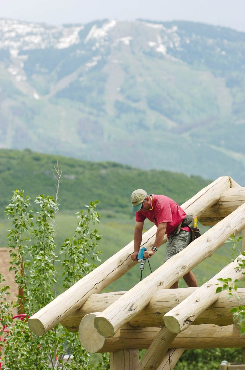 Steve Yanoski, with Scribeline Timberworks Inc. in Steamboat Springs, assembles a structure made of lodgepole pine at a picnic area in the West End Village subdivision.