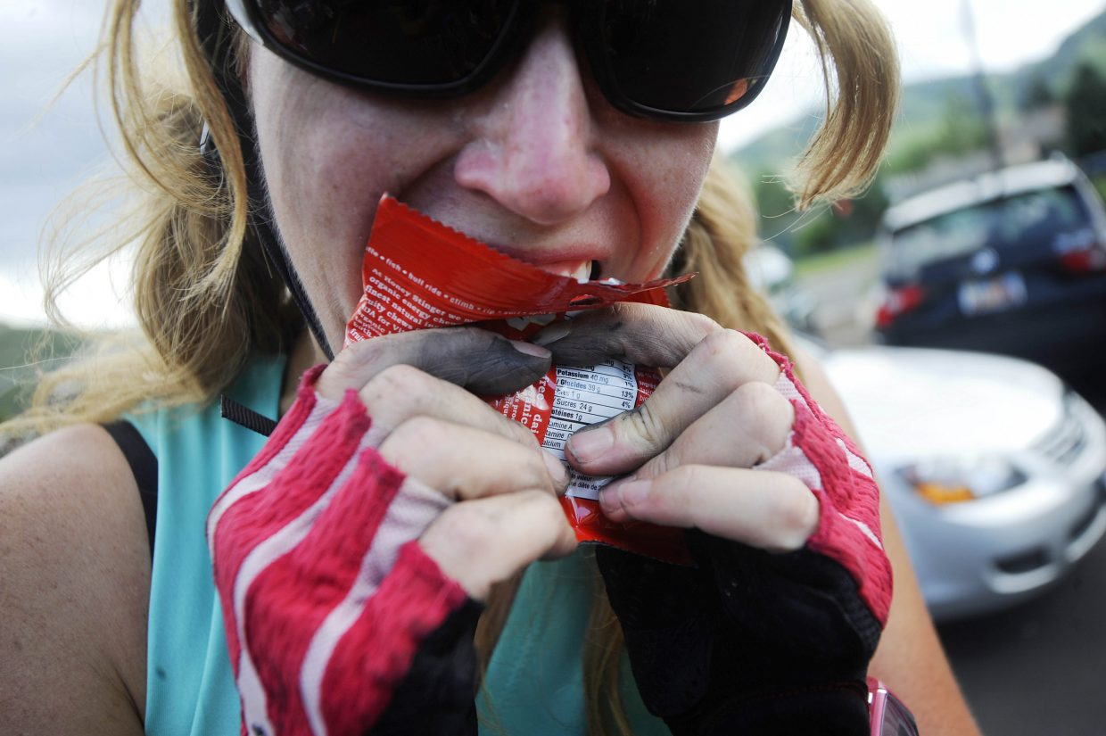 Kelly Gorder tries to open a bag of energy chews with her grease-stained fingers.