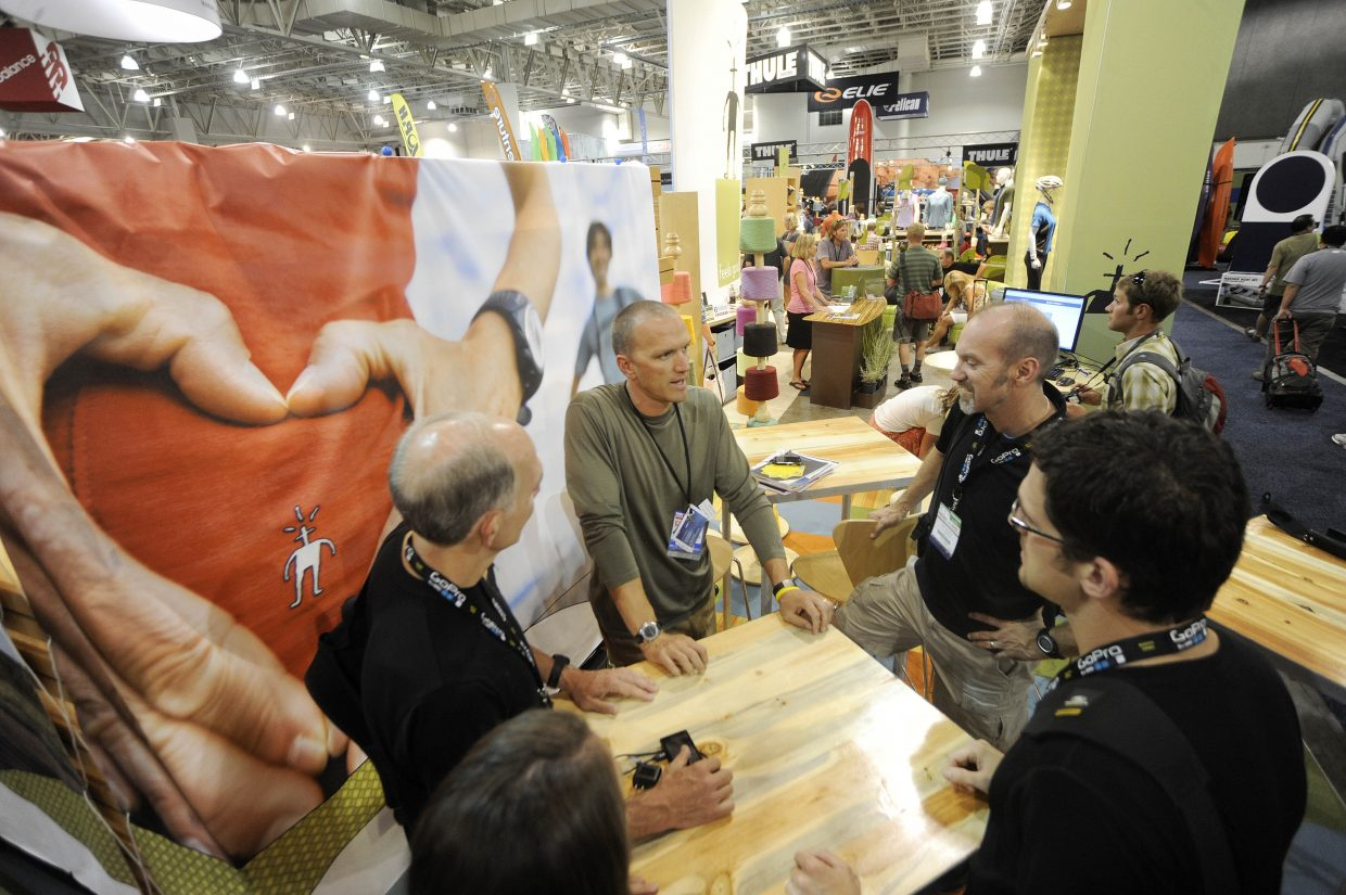 SmartWool President Mark Satkiewicz, center, visits with buyers from Michigan-based Playmakers Athletic Footwear & Apparel during the opening day of the Outdoor Retailer Summer Market trade show in Salt Lake City on Aug. 3.