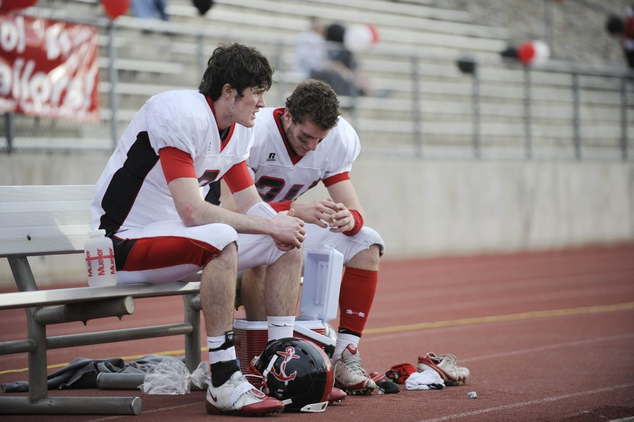 Austin Hinder, left, talks to Joe Dover as he ices an injured ankle.