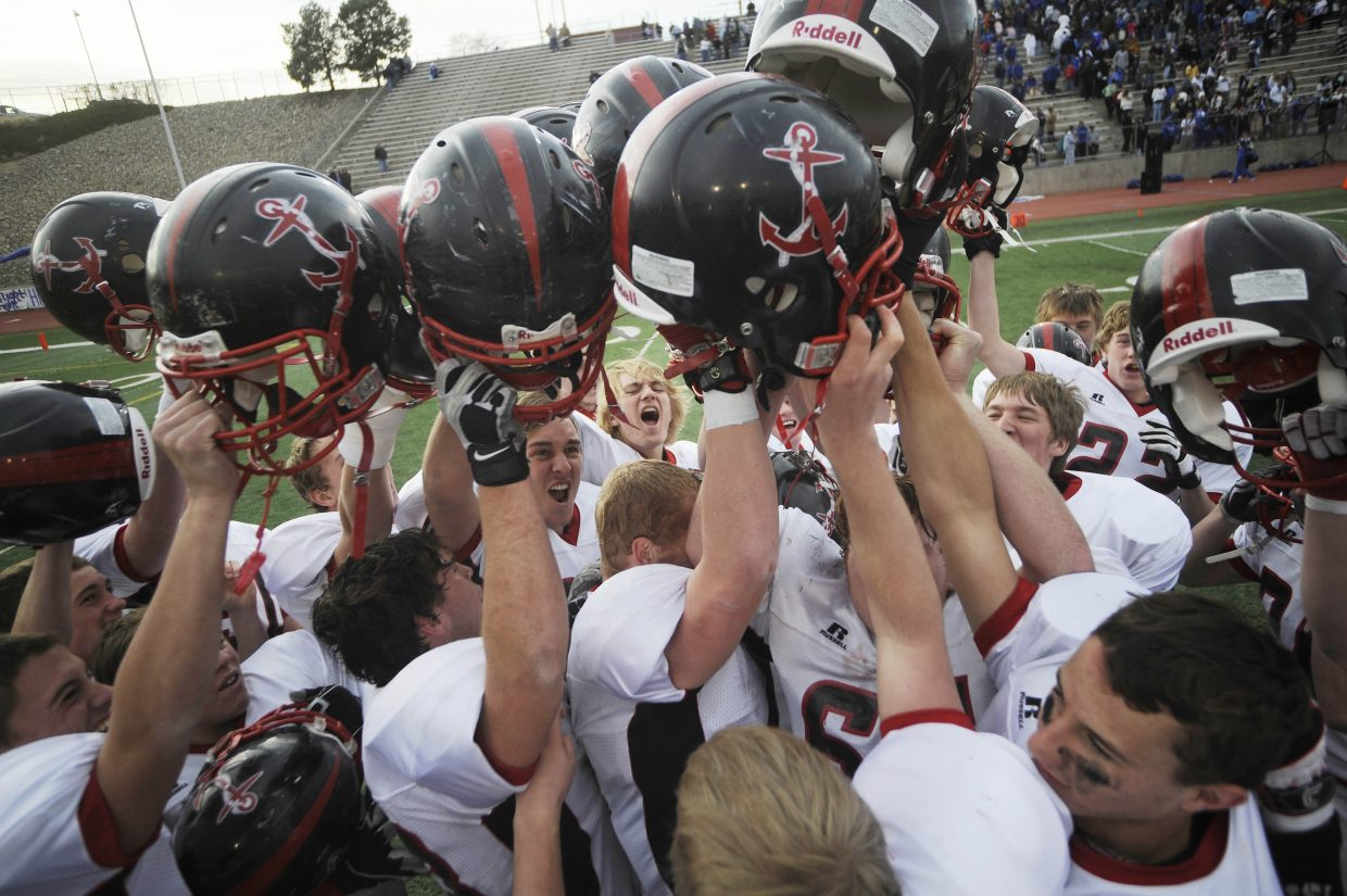 Steamboat Springs High School football players raise their helmets in victory after Saturday's win over Pueblo Central.