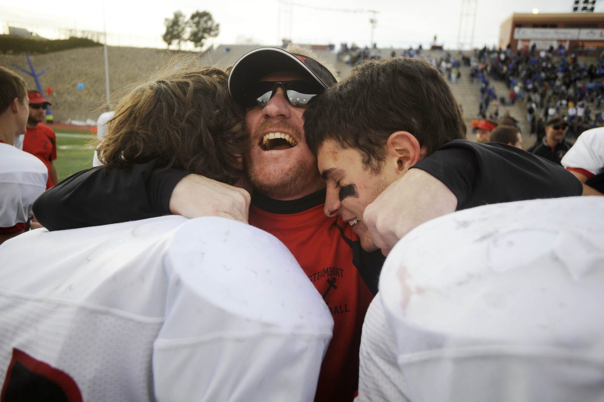 Steamboat Springs High School assistant football coach Jerry Stabile celebrates with seniors Bryce Mayo, left, and Mitchell Lekarczyk after Saturday's win over Pueblo Central.
