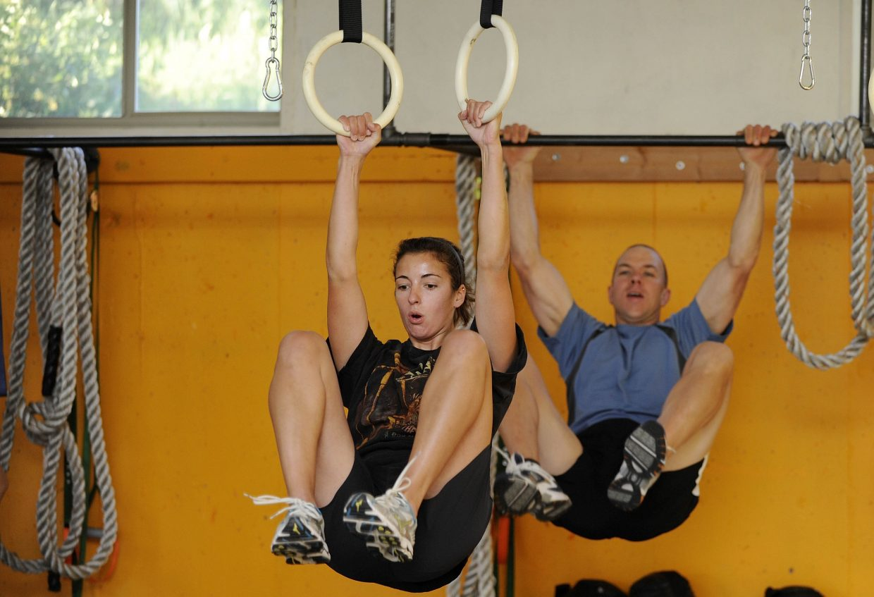 Lauren Zajic and Scott Kempers bring their knees to their elbows for a core exercise.