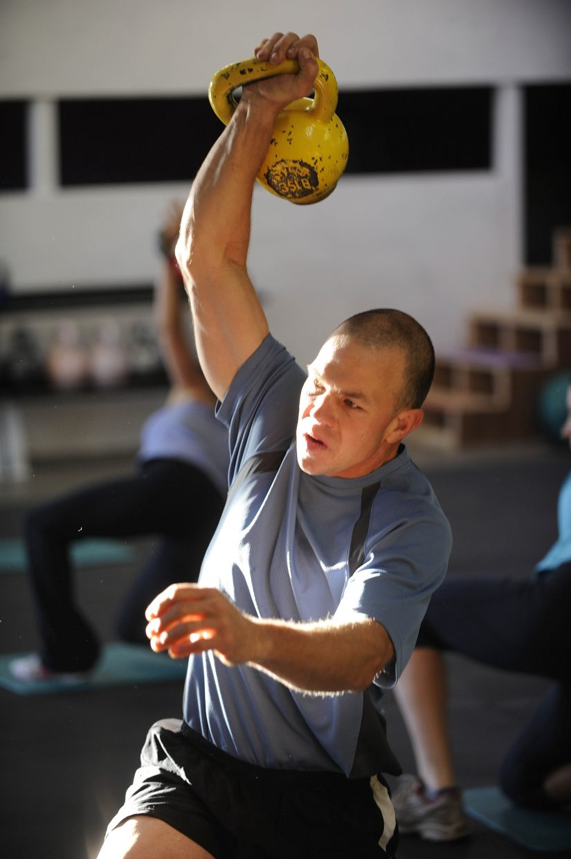 Scott Kempers performs a Turkish get-up using a kettlebell.