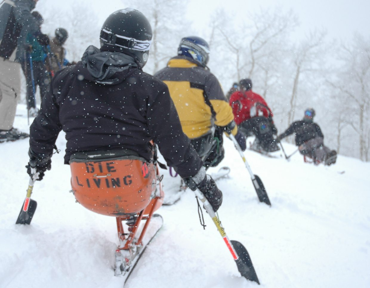Andy Campbell, front, peers down Rainbow trail Saturday at the Steamboat Ski Area with a group of monoskiers at the All Mountain Ski Camp led by Matt Feeney, second from right, and Craig Kennedy, right.