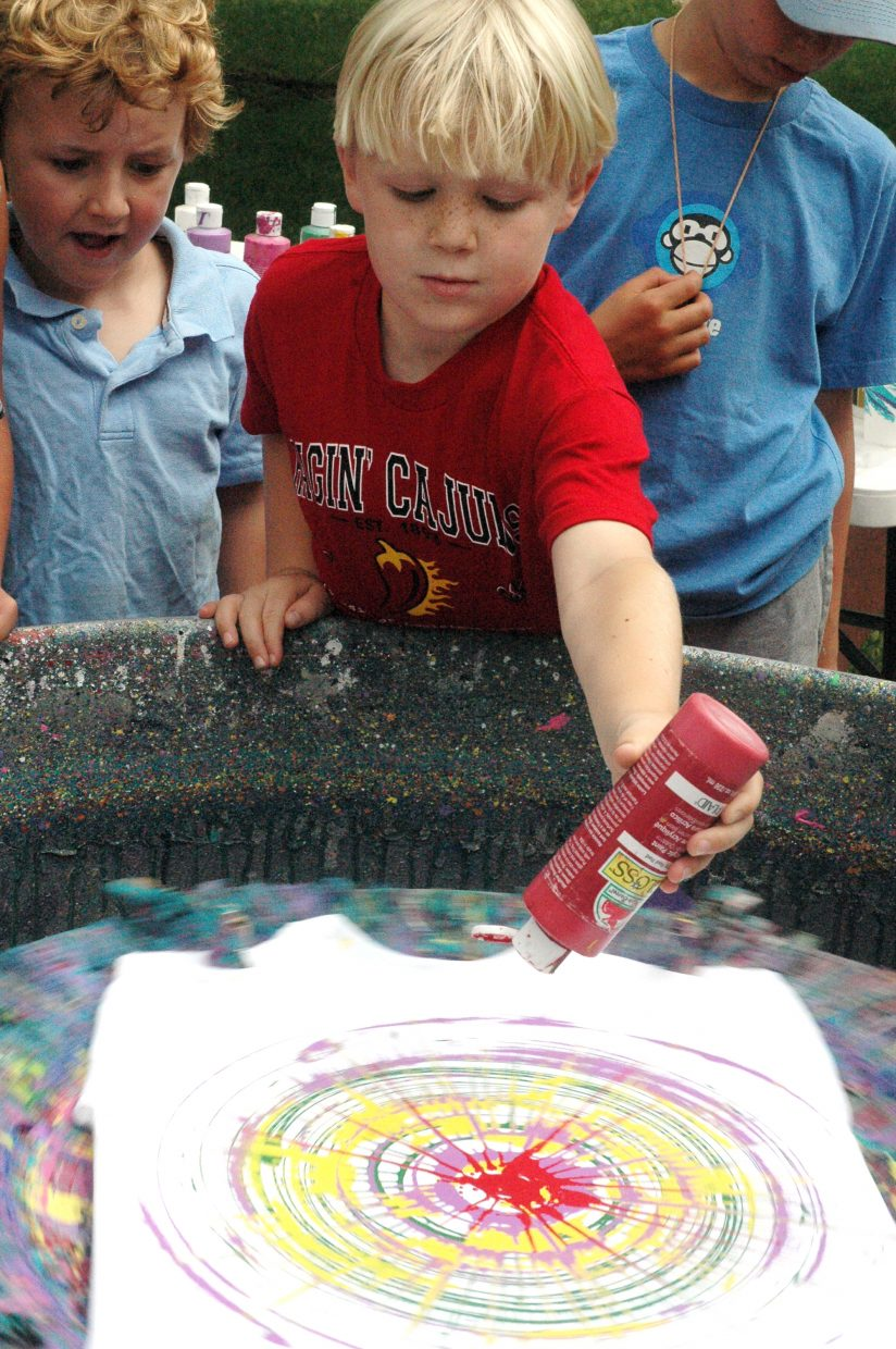 """Isaac Reiber, 7, creates a work of """"spin art"""" at an Art in the Park booth run by locals Charlie and Gail Holthausen on Saturday in West Lincoln Park. The annual Steamboat Springs Arts Council event continues Sunday."""