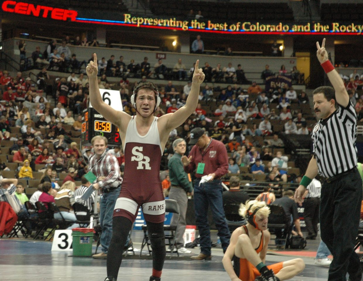 Soroco senior Levi Gonzales celebrates his overtime victory over Wiggins' Dillon McCombs (sitting, dejected and crying) in the 2A state championship 125-pound quarterfinals as the referee signifies Gonzales two winning takedown points.